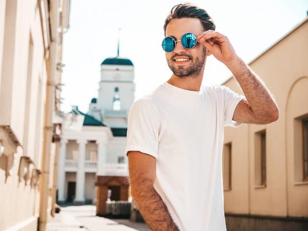 Hombre con gafas de sol con camiseta blanca posando