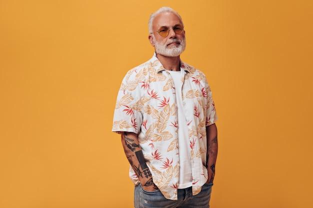 Hombre con gafas de sol naranjas y camisa mira al frente en la pared naranja