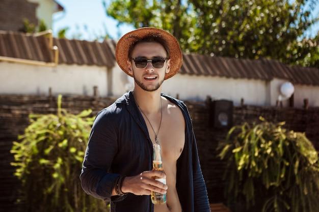 Hombre con gafas de sol y sombrero bebiendo cerveza, descansando en casa de campo