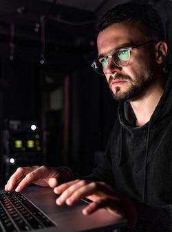 Un hombre con gafas trabaja en una computadora a altas horas de la noche.