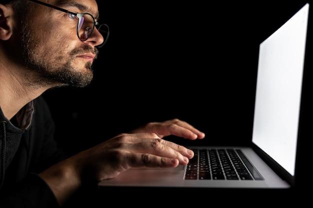 Un hombre con gafas trabaja en una computadora portátil en la oscuridad.
