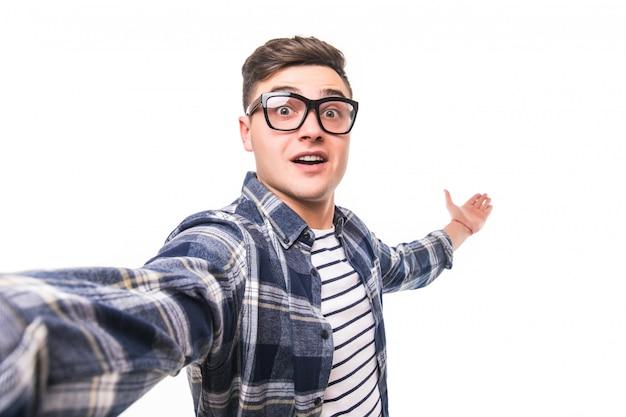 Hombre de gafas transparentes tomando un selfie aislado en la pared blanca