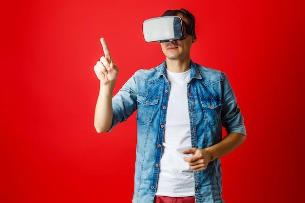 Un hombre en gafas virtuales 3d sobre fondo rojo.