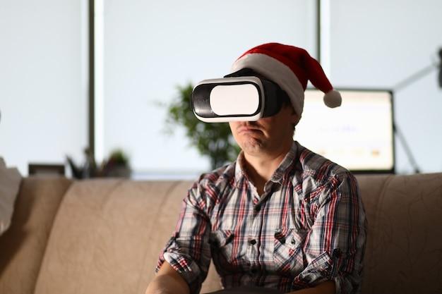 Hombre de gafas virtuales se sienta en el sofá con sombrero de santa claus