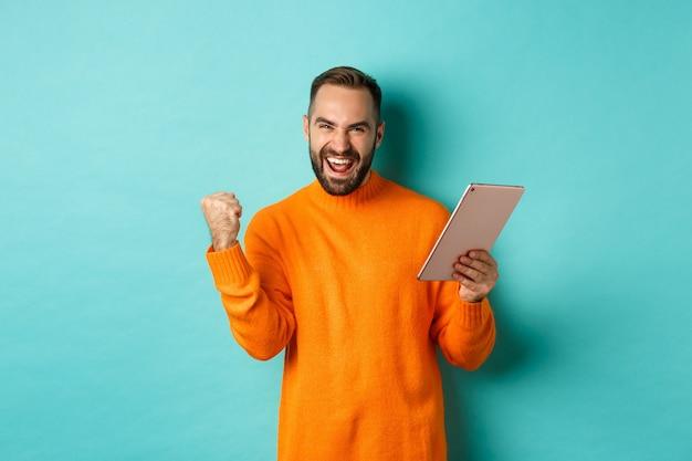 Hombre ganador alegre que sostiene la tableta digital, regocijándose y celebrando la victoria en el juego, haciendo el puño