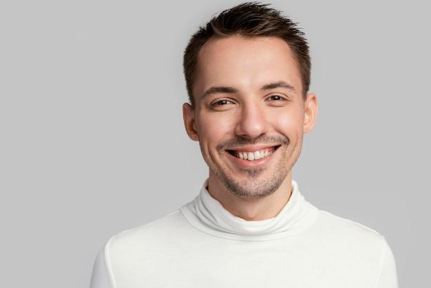 Hombre gay sonriente en blusa blanca