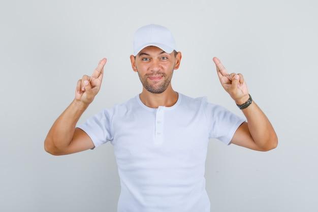 Hombre gesticulando con el dedo cruzado y deseando suerte en camiseta blanca, gorra y mirando feliz, vista frontal.