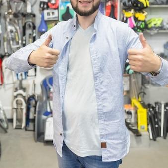 Hombre gesticulando pulgares arriba en el taller de bicicletas