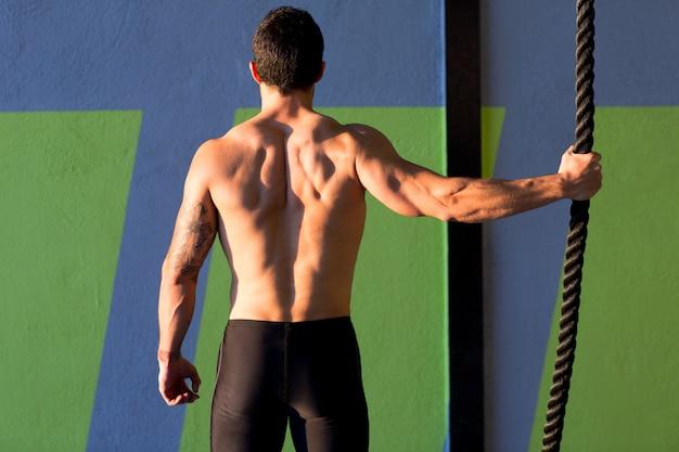Hombre de gimnasio de crossfit con mano una cuerda de escalada