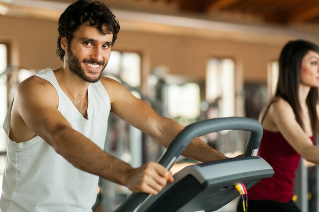 Hombre en el gimnasio, ejercitando sus piernas haciendo cardio entrenando en bicicleta