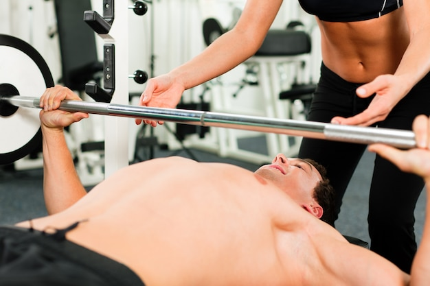 Hombre en el gimnasio haciendo ejercicio con barra