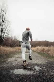 Hombre de gimnasio saludable corriendo en pista forestal