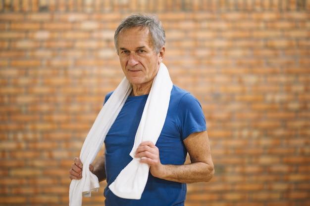 Hombre en gimnasio con toalla