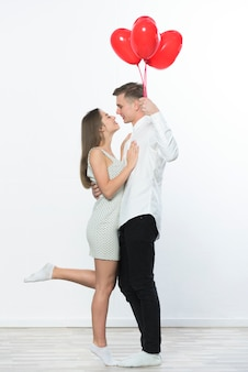 Hombre con globos de corazón abrazando a mujer