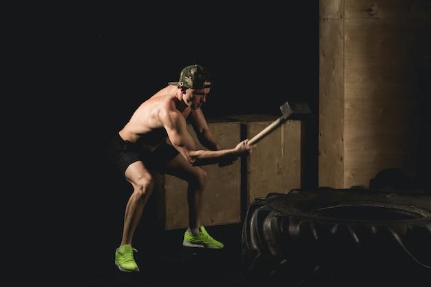 El hombre golpea a tyre. entrenamiento en el gimnasio con martillo y neumático de tractor siluet