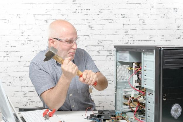Hombre golpeado con un martillo en la computadora