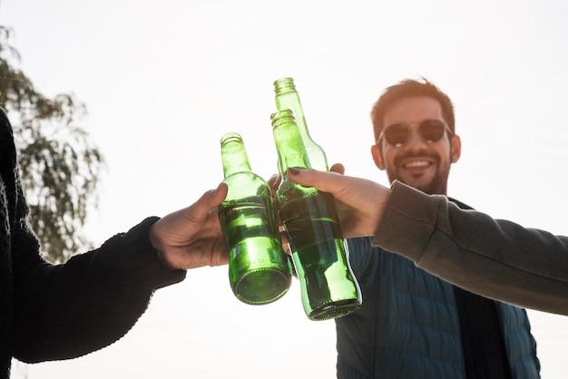 Hombre golpeando botella de cerveza con amigos