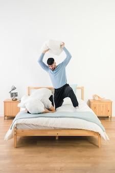 Hombre golpeando a su novio con almohada blanca en cama