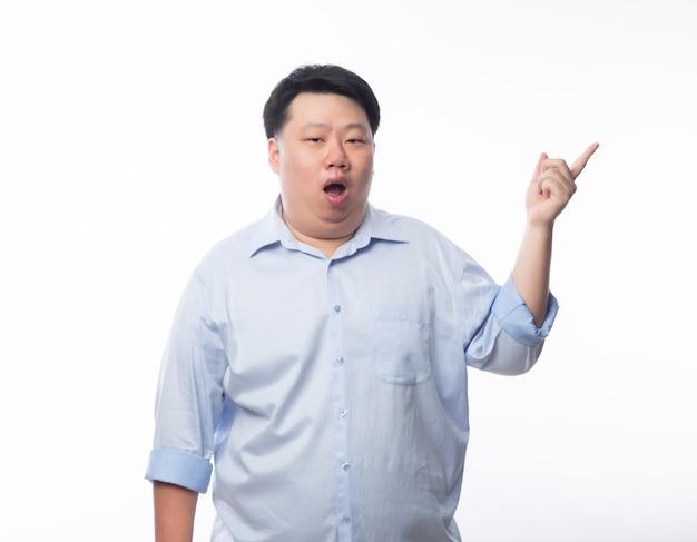 Hombre gordo asiático en camisa azul apuntando a copyspace con cara de dudas aislado