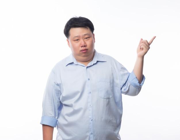 Hombre gordo asiático en camisa azul pensando y señalando copyspace con cara de dudas aislado en la pared blanca