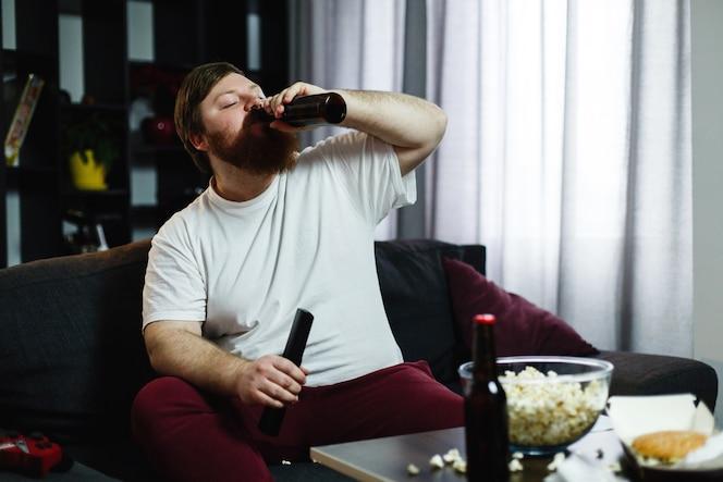 Hombre gordo bebe cerveza tumbada en el sofá