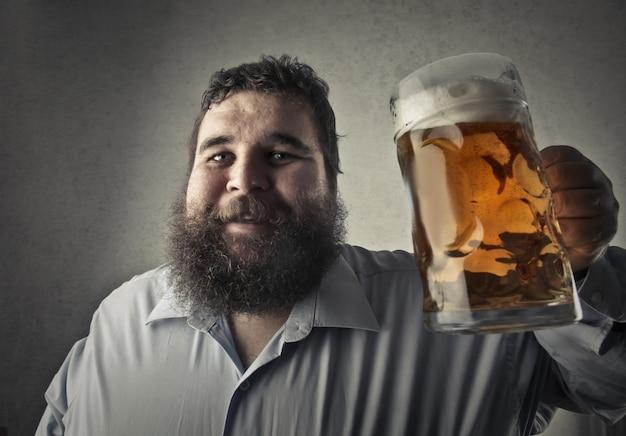 Hombre gordo bebiendo una cerveza