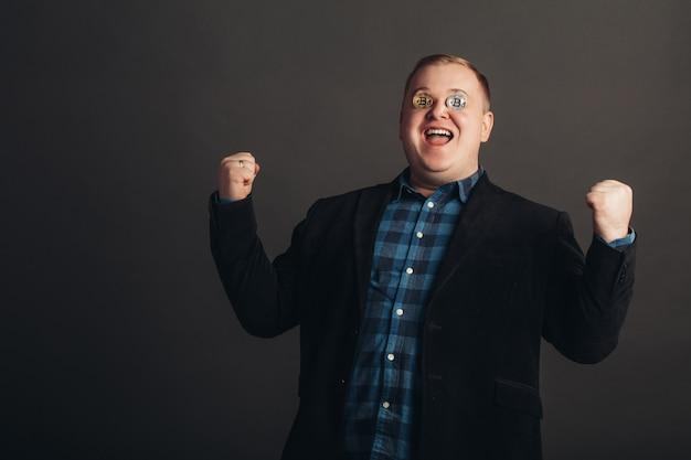 Hombre gordo celebrando una cara loca amante loco de bitcoin con una moneda de oro en los ojos