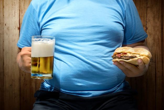 Hombre gordo con cervezas y hamburguesa en la mano.