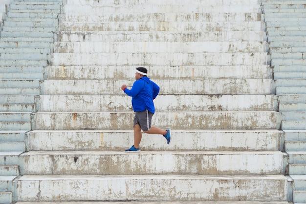 Hombre gordo corriendo por las escaleras