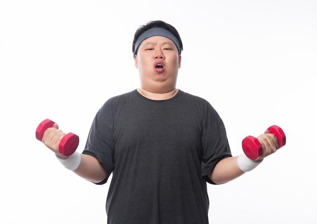 Hombre gordo divertido asiático en ropa deportiva haciendo ejercicio con pesas