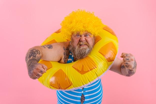 Hombre gordo enojado con peluca en la cabeza está listo para nadar con un salvavidas de rosquilla