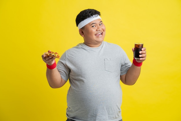 Hombre gordo es feliz comiendo pizza y bebiendo cola