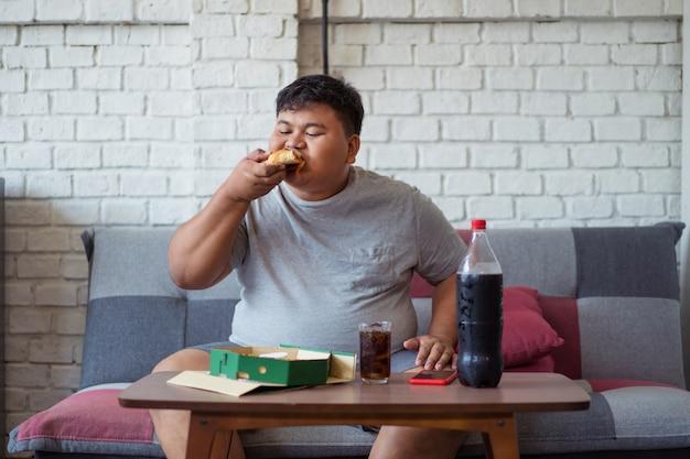 Hombre gordo feliz es feliz mientras come pizza