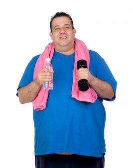 Hombre gordo en el gimnasio con una botella de agua aislada sobre un fondo blanco