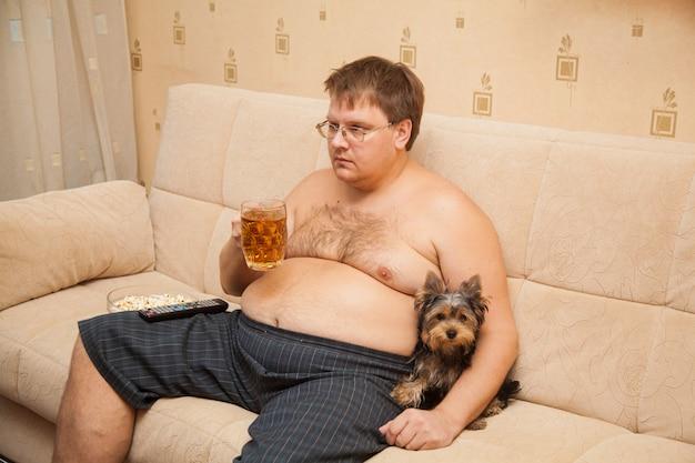 Hombre gordo con panza de cerveza frente a tv come palomitas de maíz con su mascota