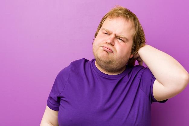 Hombre gordo pelirrojo auténtico joven que sufre dolor de cuello debido al estilo de vida sedentario.