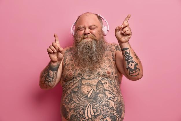 Hombre gordo relajado y divertido con cuerpo desnudo, brazos y estómago tatuados, baila mientras escucha música, mueve los brazos y cierra los ojos con alegría, usa audífonos en las orejas, se divierte y siente aspiración