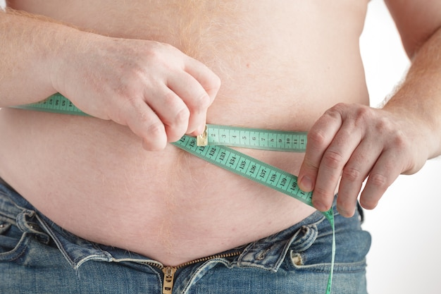 Hombre gordo revise su grasa corporal con cinta métrica para la grasa u obesidad