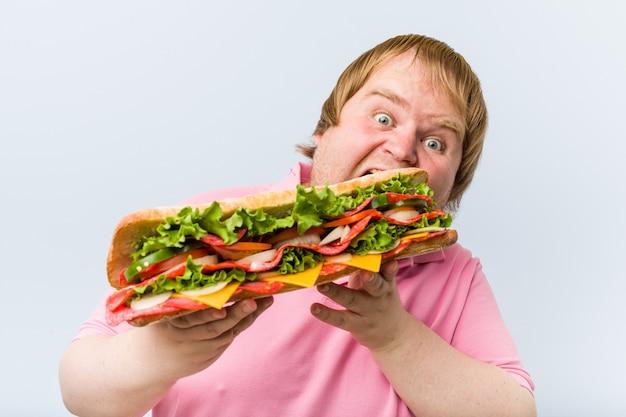Hombre gordo rubio caucásico loco sosteniendo un sándwich gigante