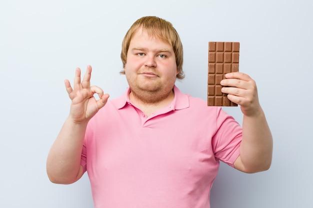 Hombre gordo rubio caucásico loco sosteniendo una tableta de chocolate