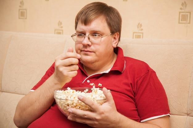 Hombre gordo viendo la televisión comiendo palomitas de maíz