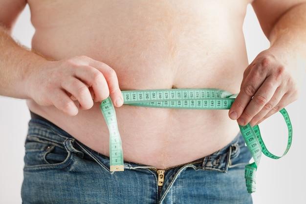 Hombre gordo vientre con cinta métrica. perder peso concepto.