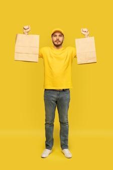 Hombre de gorra amarilla, camiseta dando paquetes de papel aislados. mensajero empleado masculino mantenga paquetes de papel con comida