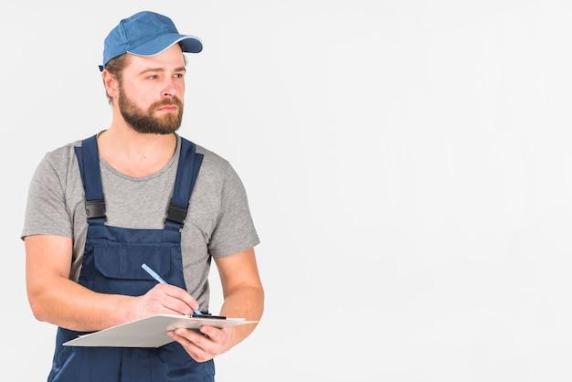 Hombre en gorra y escritura general en portapapeles