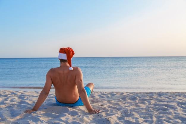 Hombre con gorro de papá noel en la playa