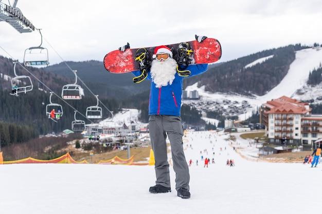 Un hombre con un gorro de papá noel con una tabla de snowboard en una estación de esquí.