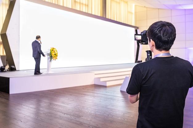 Hombre grabando un altavoz con pantalla de pared blanca para presentación