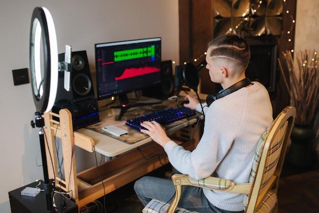 Hombre grabando video en el teléfono inteligente durante el trabajo en casa en la computadora joven grabando en