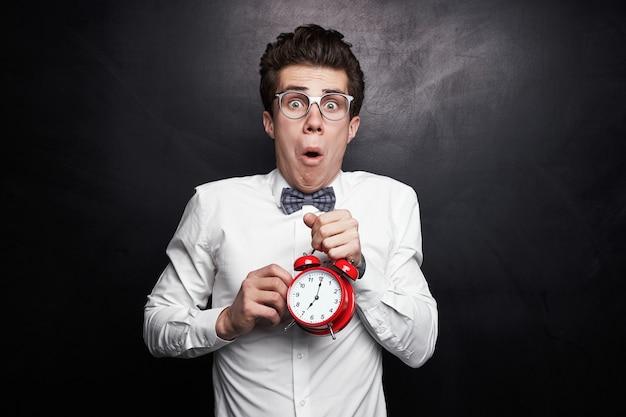 Hombre gracioso asombrado con gafas sosteniendo el despertador y mirando a la cámara mientras llega tarde a los estudios contra el fondo negro