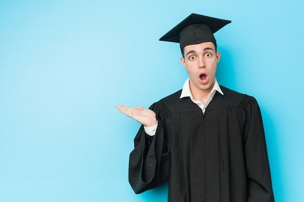 El hombre graduado caucásico joven impresionó llevar a cabo el espacio de la copia en la palma.